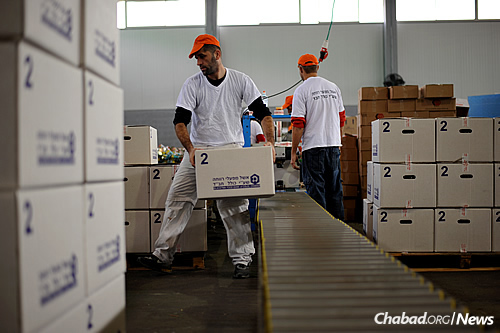 Workers pack boxes of nutritious items, such as quinoa, and whole-wheat pasta and couscous, for distribution to those dealing with food insecurity. (Photo: Colel Chabad)