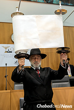Chasia Feldman's father, Michael Kiel of Jerusalem, lifts the Torah for all to see. (Photo: Andrew Taylor)