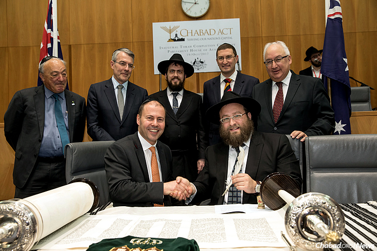 Rabbi Eli Gutnick, right, finishes the final letter of a new Torah in the Canberra Parliament House, witnessed by The Hon. Josh Frydenberg, MP, seated next to him. Standing, from left, are Dr. Mike Freelander, MP; The Hon. Mark Dreyfus, MP; Rabbi Shmueli Feldman, co-director of Chabad ACT in Canberra; Julian Leeser, MP; and the Hon. Michael Danby, MP. Behind them is Menachem Feldman. (Photo: Andrew Taylor)