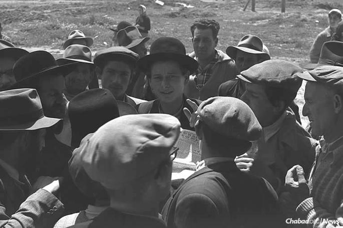 Distraught villagers of Kfar Chabad, both young and old, gather around a newspaper carrying reports of the attack. (Photo: Moshe Pridan/Israel Government Press Office)