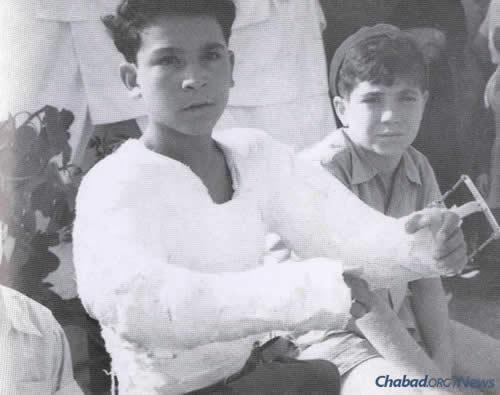 A young boy injured by bullets during the attack on Beit Sefer Lemelecha attends the groundbreaking of the new printing school, named Yad Hachamisha in memory of the victims. (Photo courtesy of Yimei Temimim Archive)
