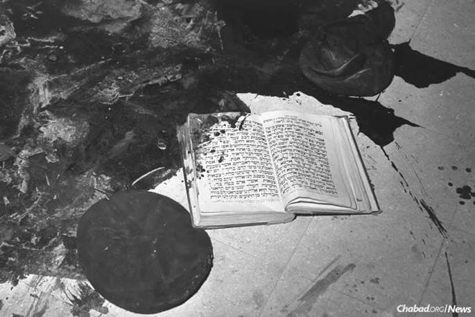 The attack, which prompted an outcry by Israel at the United Nations, shocked the young country and the world. This image of a blood-stained prayerbook on a blood-soaked floor symbolized the horror of the attack. (Photo: Moshe Pridan/Israel Government Press Office)