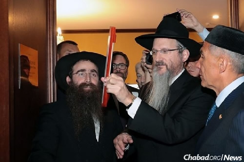 Lazar affixes the mezuzah to the yeshivah doorpost.