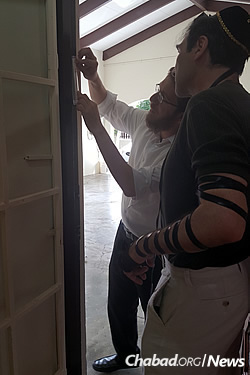 Rabbi Refoel Silver, left, affixes a mezuzah to his family's new home.