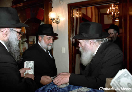 Hadad, center, receives a dollar from the Rebbe.