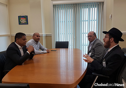 The rabbi, right, and Ivan Becher, to his right, meet with the prime minister of Curaçao, Eugene Rhuggenaath, at left.