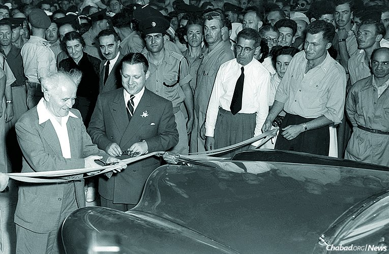 "Israeli Prime Minister David Ben-Gurion, left, cuts the ribbon at the opening of the Kaiser-Illin auto plant in Israel as its owner, Efraim Illin, a titan of Israeli industry, looks on. An interview with Illin is one of 41 accounts showcased in ""My Story,"" a collection of first-person narratives of encounters with the Rebbe—Rabbi Menachem M. Schneerson, of righteous memory—presented with photographs and related images. (Photo: Fritz Cohen/GPO)"