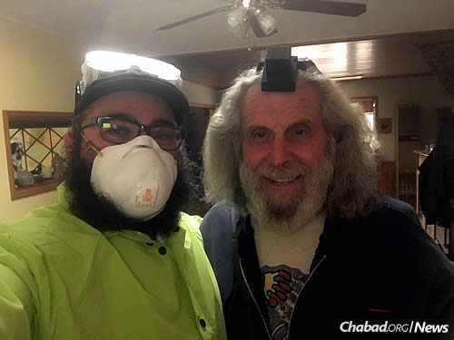 Nemtzov wraps tefillin with a local Jewish man.
