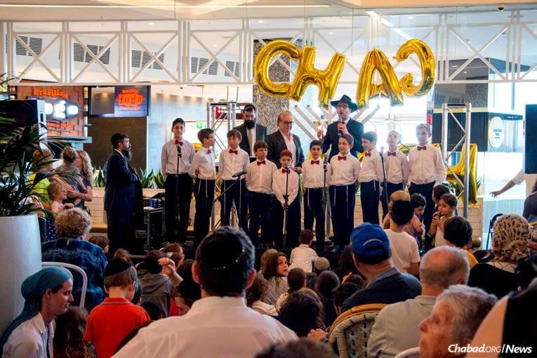 Le Rav 'Habad Levi Wolf dirige une chorale de garçons lors de la cérémonie d'allumage organisée par la Central Synagogue au centre commercial Westfield Bondi à Sydney, en Australie, mardi 12 décembre dernier, la première nuit des huit jours de fête de 'Hanouka. (Photo : Alon Bar David)