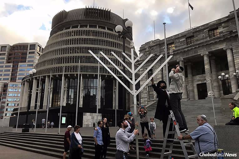 Chabad-Lubavitch Rabbi Mendel Goldstein, left, assists in lighting the first public menorah this Chanukah (5778) at the Parliament House in Wellington, New Zealand, on Tuesday, Dec. 12, the first night of the eight-day holiday.