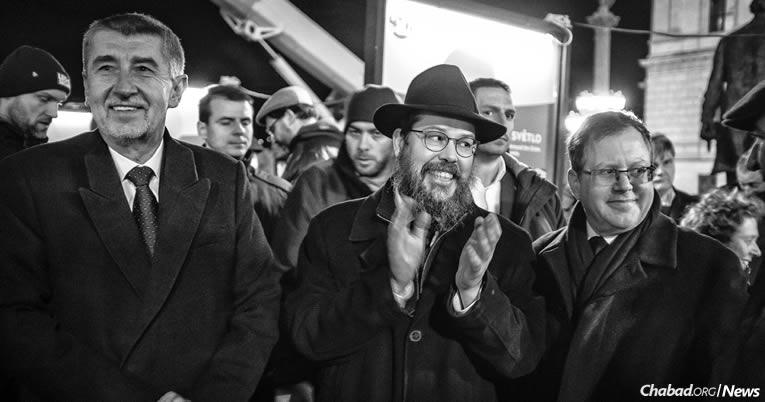 Andrej Babis, Premier ministre de la République tchèque, à gauche, et l'ambassadeur d'Israël en République tchèque Daniel Meron, à droite, entourent le Rav Manis Barash à l'allumage de Prague mardi 12 décembre, la première nuit de la fête de 'Hanouka. (Photo : Karl Cudlín)