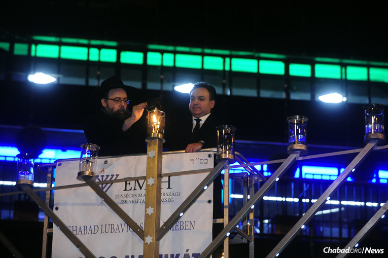Rabbi Boruch Oberlander, left, director of Lubavitch of Hungary, and violinist Zoltán Mága usher in the initial of daily celebrations related to the 20th anniversary of Chanukah menorah-lightings in Budapest, on Tuesday, Dec. 12, the first night of the eight-day holiday.