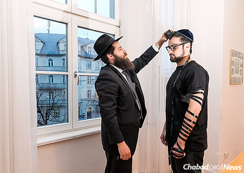 Gordon helps photographer Mitya Kolomiyets put on tefillin. In the background is the building in which Hitler once lived.