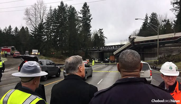 Washington Gov. Jay Inslee, center, inspects the site of an Amtrak train that derailed in DuPont, Wash., which resulted in the deaths of three passengers and more than 100 people injured at the height of rush hour on Monday morning. (Photo: Washington Governor's Office)