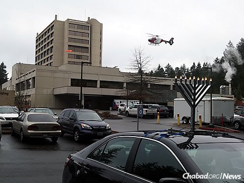 Rabbi Schtroks's menorah-topped car, in front, in the parking lot of Providence St. Peter Hospital in Olympia, where he spent time with families of passengers being treated.