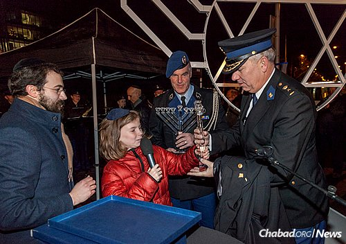 Rabbi Yanki Jacobs, left, looks on as children from a Jewish school present inscribed crystal menorahs to members of security forces. (Photo: DPHOTO/Dirk P.H. Spits)
