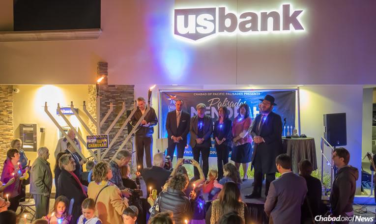 L'acteur Billy Crystal, au centre, a allumé la Ménorah lors d'un événement organisé par le Rav Zushe et Mme Zisi Cunin qui dirigent le centre 'Habad de Pacific Palisades en Californie, et par le Rav Eli et son épouse Elka Baitelman qui officient dans ce centre. Billy Crystal était accompagné de son épouse Janice et, à sa gauche, de Rick Caruso, propriétaire du nouveau centre de Palisades Village où l'allumage a eu lieu mardi 12 décembre, le premier des 8 soirs de 'Hanouka.