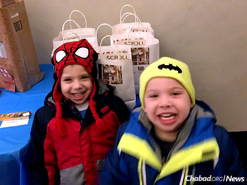 Four-year-old twins Joshua and Mason Weitz pick bags up on Fridays at Kiddie Korner to deliver to area seniors. Inside are soup, challah, cake, Shabbat materials, and sometimes, seasonal items (this month, warm scarves).