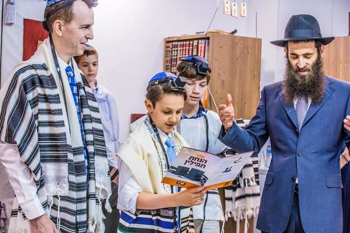 A bar mitzvah celebration can include many rituals, such as putting on tefillin. (Maitri Shah Photography)