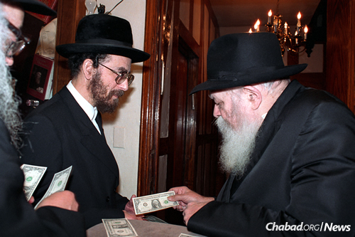 Slonim, left, receives a dollar from the Rebbe. (Photo:JEM/The Living Archive)