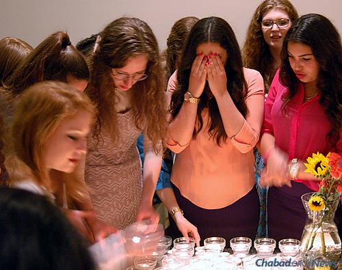 Lighting candles before Shabbat.