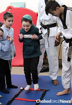 Karate is on tap for young boys, who get help from teen volunteers.