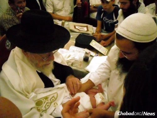 Shevach, right, a skilled mohel, performs a brit milah in Israel. (Photo: Yishai Gilad/TPS)