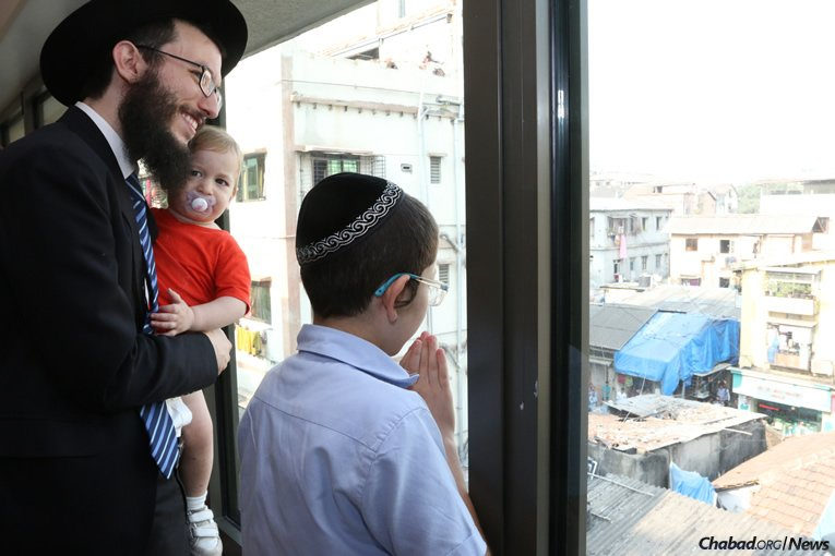 "Moshe Holtzberg, right, fondly known as ""Baby"" Moshe, together with Rabbi Israel Kozlovsky, co-director of Chabad-Lubavitch of Mumbai, look out from Nariman (Chabad) House, as well-wishers wave and blow kisses to Moshe. (Photo: Chabad of Mumbai/Chabad.org)"