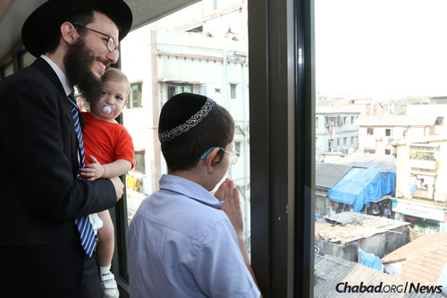 """Moshe Holtzberg, right, fondly known as """"Baby"""" Moshe, with Rabbi Israel Kozlovsky, co-director of Chabad-Lubavitch of Mumbai, and his baby, look out from Nariman House as well-wishers wave and blow kisses to Moshe. (Photo: Chabad of Mumbai/Chabad.org)"""