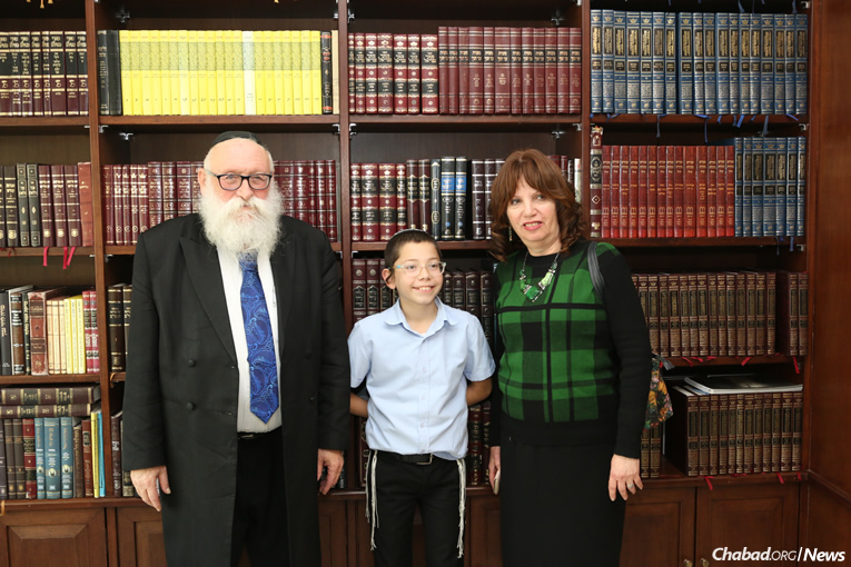 In the Nariman House library with his maternal grandparents, Rabbi Shimon and Yehudit Rosenberg. (Photo: Chabad of Mumbai/Chabad.org)