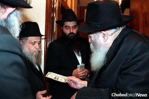 Morosov receives dollar bills from the Rebbe. (Photo: JEM/The Living Archive)