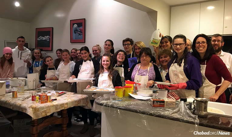 "Rabbi Shimon and Chanie Kramer, far right, who run the Chabad Center for Jewish Life in Merrick, N.Y., with teens involved in the ""Cooking for Hope"" program. For his work, the rabbi got tapped as ""Person of the Year"" by the Herald newspaper chain on Long Island, N.Y."