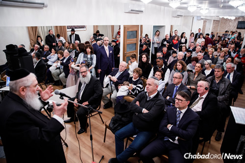 Mangel, a noted lecturer, author, translator and teacher, addresses a crowd of 200 people at the Chabad center's opening, including Slovakia's Minister of Culture Marek Maďarič (seated above, first row at right), who was on hand for the ribbon-cutting ceremony.