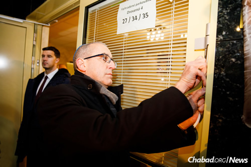 Israel's Ambassador to Slovakia Tzvi Vapni affixes a mezuzah to the Chabad center's door.