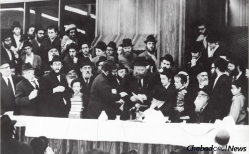 Artist Elazar Kalman (E.K) Tiefenbrun, center, at a farbengen with the Rebbe on the day before Shavuot 1975, when a special farbrengen was held to celebrate the publication of the new bilingual edition of Tanya. The Rebbe gave special attention to the guests from England and called on Tiefenbrun to come up to the dais together with his children. A pile of the new Tanya volumes can be seen to the left as Tiefenbrun says l'chaim with the Rebbe.