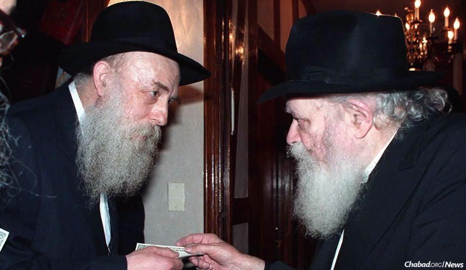 Elazar Kalman (E.K) Tiefenbrun receiving a dollar and a blessing from the Lubavitcher Rebbe.