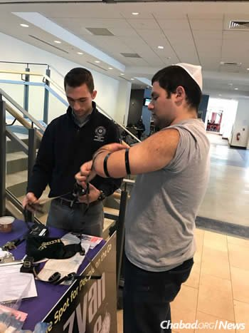 Kevin Brown, right, dons tefillin with Meir Berkman. Brown had not heard of tefillin when he arrived at Binghamton as a freshman, and now as a Jewish student leader helped lead the campus campaign.
