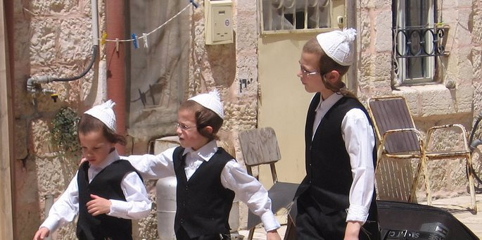 נערים משחקים בחצר בשכונת מאה-שערים בירושלים. לראשיהם כיפה ירושלמית לבנה