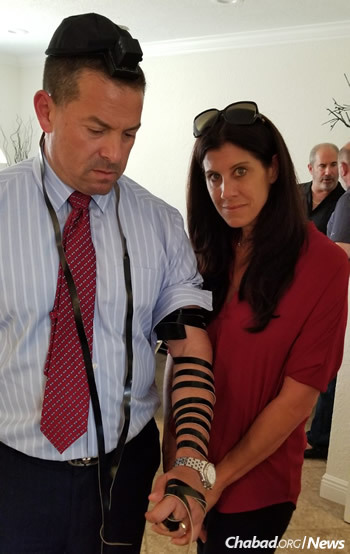 Michael Udine, commissioner of Broward County, puts on tefillin in the Pollack home next to his wife, Stacey.