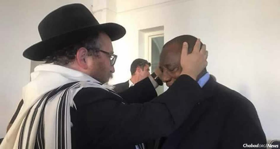 President Cyril Ramaphosa of South Africa receives a blessing from Rabbi Asher Deren, chairman of the Rabbinical Association of the Western Cape.