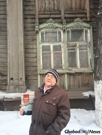 Tomsk Jewish historian David Kuzhner holds a book he wrote on the Jewish history of the Siberian city outside the Soldiers' Synagogue.
