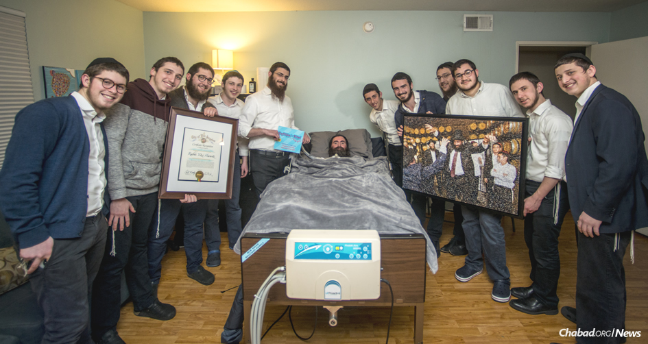 Yeshivah students gathered at the bedside of Rabbi Yitzi Hurwitz and presented him with a digital portrait composed of thousands of miniaturized images of men, women and children around the world doing mitzvahs in honor of his 46th birthday. (Photo: Mushka Lightstone/Chabad.org)
