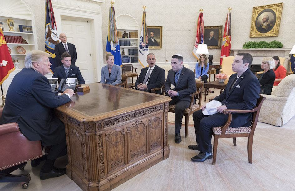 """Meadow Pollack's family meeting with President Donald Trump, left, at the White House. Her brother, Hunter, says he wore a kippah to send a message that his peers should """"be proud to be Jewish."""" From left, around the desk: Brandon Schoengrund, Julie Phillips-Pollack, Andrew Pollack, Hunter Pollack and Huck Pollack. Standing by the door is White House Chief of Staff John Kelly. (Official White House Photo by Shealah Craighead)"""