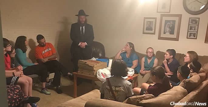 Rabbi Shaya Denburg, center, at the Florida home of a student who survived the mass shooting at Marjory Stoneman Douglas High School in Parkland. The student's parents, as well as friends and their parents, attended the gathering. The teen will be among those attending the Shabbaton in New York this weekend.