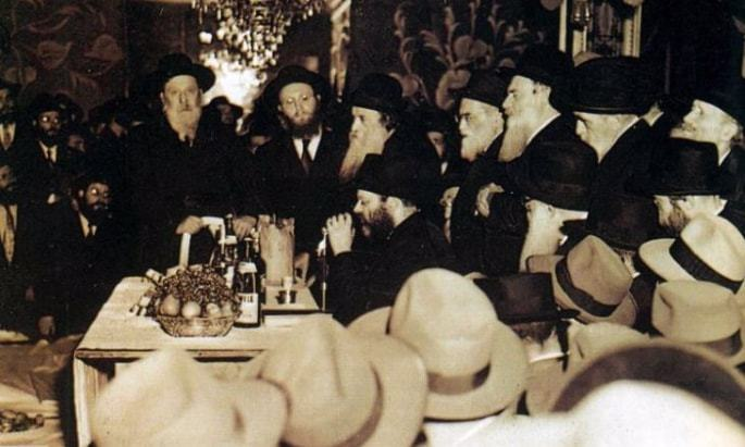 Senior Chassidim stand to listen as the Rebbe recites a Chassidic Discourse at a farbrengen held at a rented hall in the 1950s.