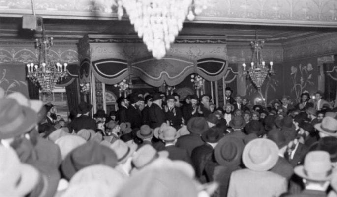 The Rebbe dances and sings in his place at a Yud Tes Kislev gathering held in a rented hall in 1954.