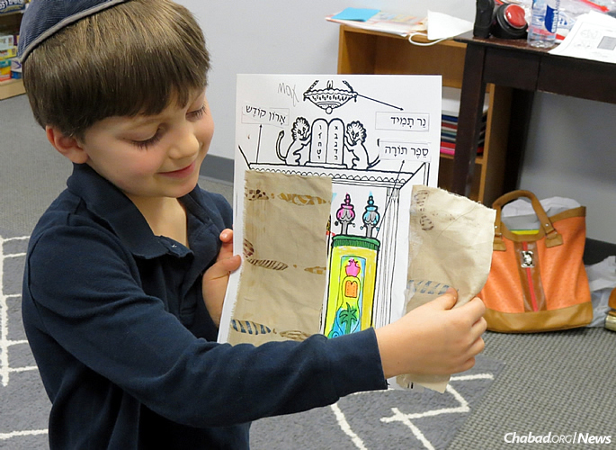 A first-grader displays his project after learning how and where a Torah is kept.