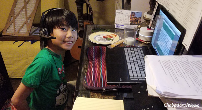 Matan Ogorek enjoys a glass of milk and a snack while learning online.