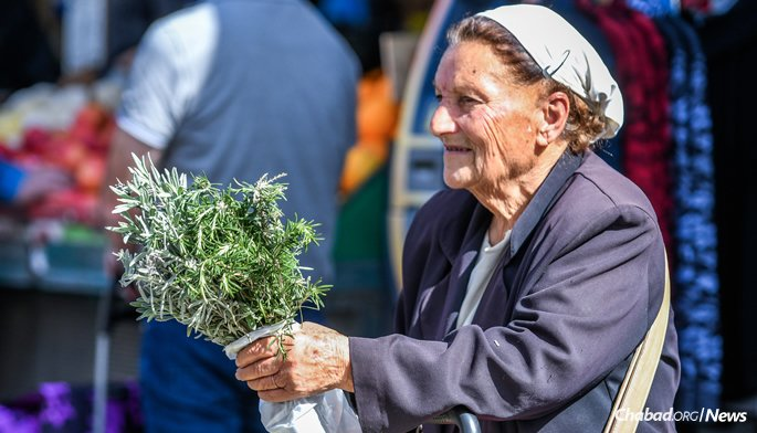 A woman sells hand-picked rosemary. (Photo: Aviad Tevel)