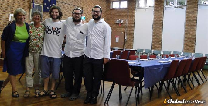 Rabbinical students Mendel, fourth from left, and Levi Super get set for the Passover Seder with Jewish residents in rural Australia.